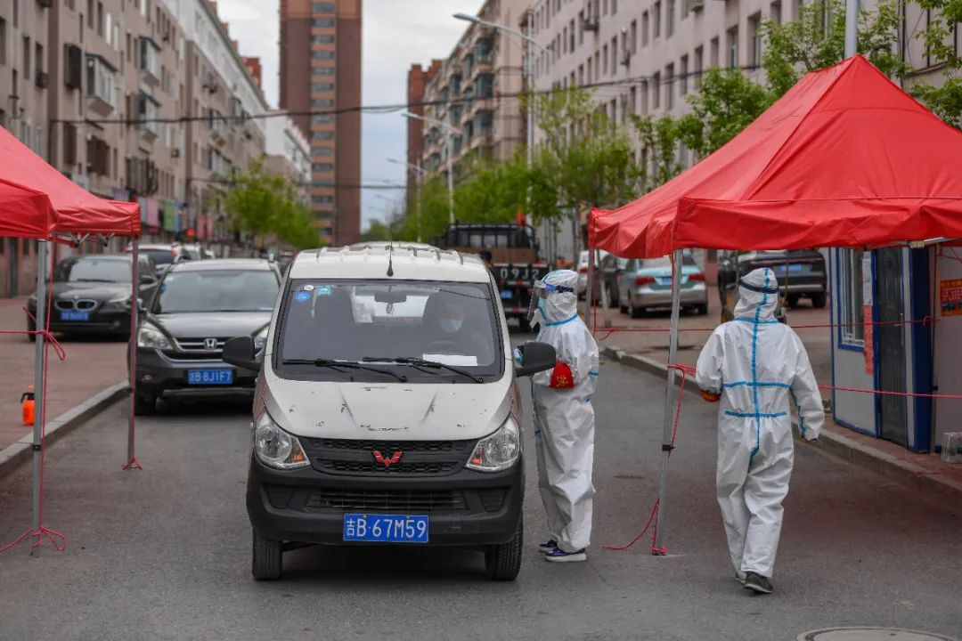 5月18日,在舒兰市某小区,事情职员为收支住民测温挂号。