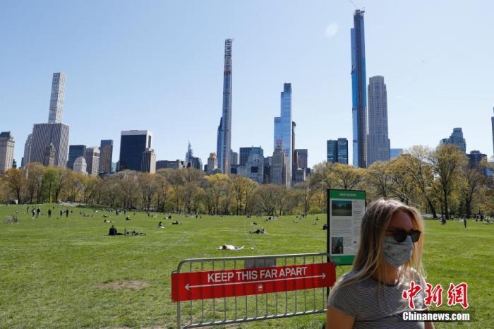 当地时间4月28日,新冠肺炎疫情下的纽约中央公园草坪树立警示牌,提醒人们保持社交距离。 中新社记者 廖攀 摄