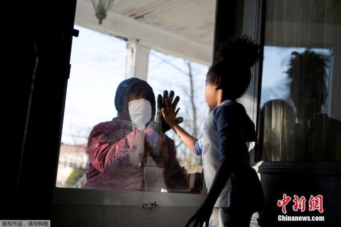 """当地时间4月11日,美国纽约州新冠疫情持续严峻,新罗谢尔市的医疗行业从业人员哈希姆在工作期间与家人保持""""社交距离"""",和女儿隔门相会击掌。"""