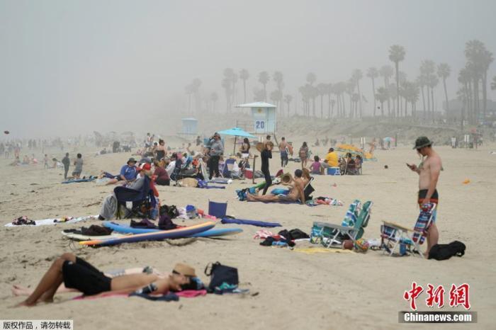当地时间4月25日,美国加州亨廷顿海滩,民众无视保持社交距离的建议,成群结队在海边晒太阳度周末。