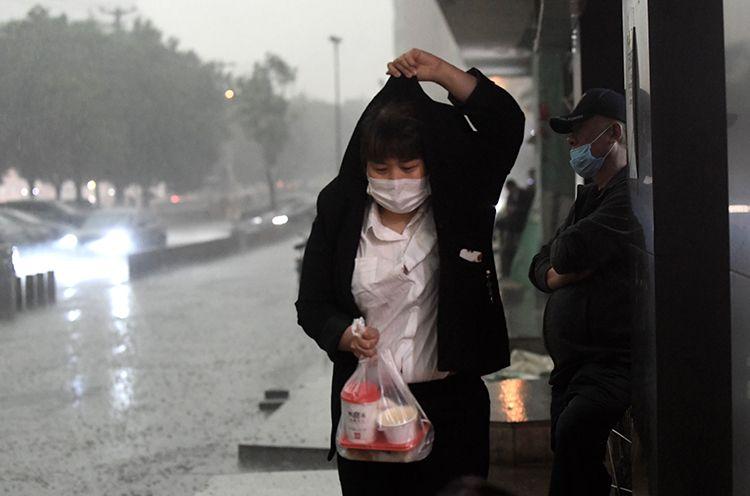 15时59分,广渠路,行人冒雨出行。