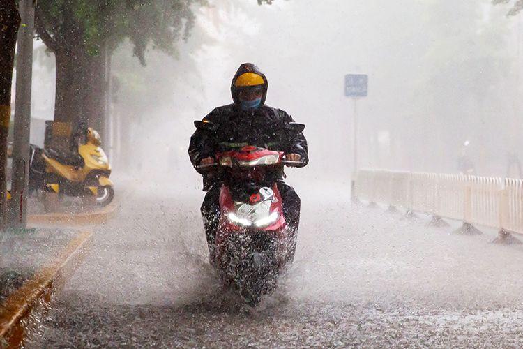 15时54分,海淀区文慧园路,行人骑车冒雨出行。