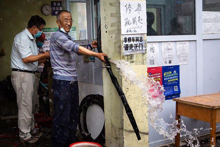 15时58分,海淀区文慧园路,市民向外排水。