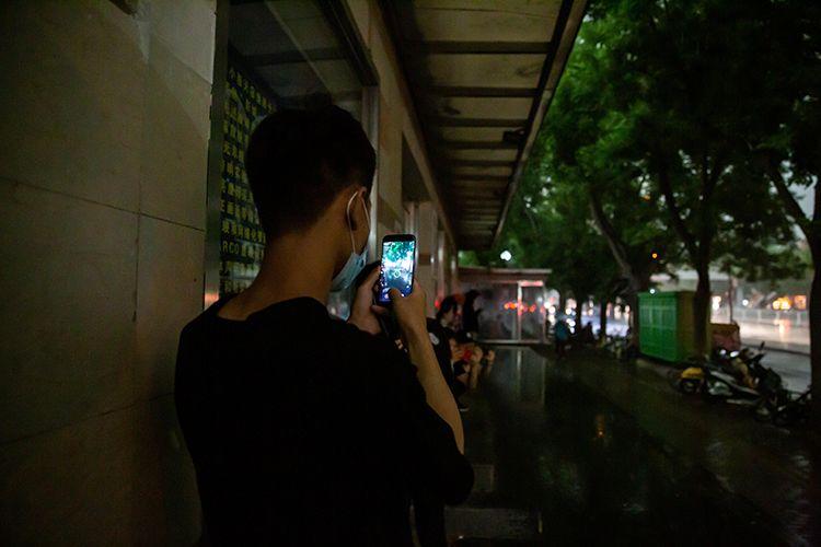 15时47分,躲雨的小伙在拍摄大雨。