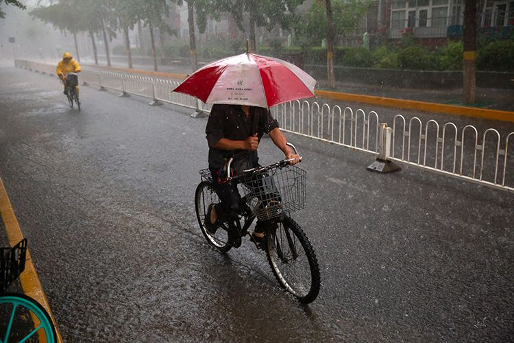 15时53分,海淀区文慧园路,行人打伞骑车出行。