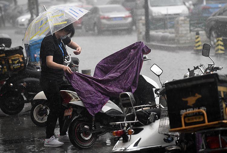 16时05分,广渠路,行人雨中遮盖电瓶车。