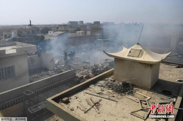 当地时间5月22日,巴基斯坦国际航空公司(PIA)一架拉合尔飞往卡拉奇的PK8303客机在该国南部卡拉奇市郊居民区坠毁。图为飞机坠毁现场,部分建筑物受损严重。