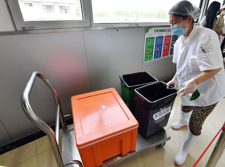 门生用餐完毕,食堂事情职员将垃圾接纳。