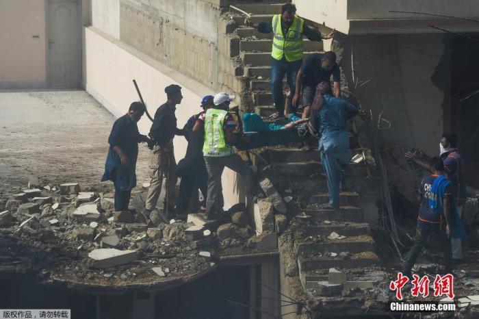 当地时间5月22日,巴基斯坦卡拉奇,志愿者在飞机失事现场将一名伤者抬出废墟。