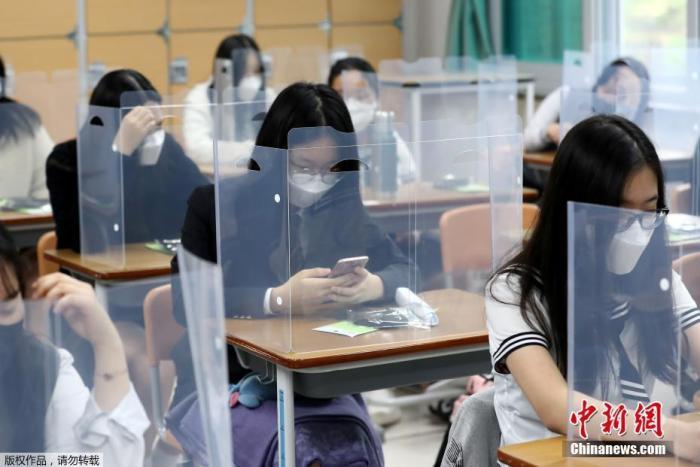 当地时间5月20日,韩国高三学生复课,韩国大田一所学校的课桌上安装了塑料挡板以防止病毒传播。韩国本计划于上周分阶段实现开学,但受首尔娱乐场所集体感染影响,开学推迟到本周。