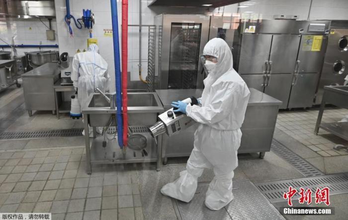 当地时间5月11日,韩国,首尔一所高中的食堂,卫生官员穿着防护服喷洒消毒剂。