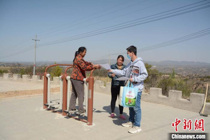趁休息间隙,刘勇给路边村民发放宣传资料,讲解防疫知识。 侯耀强 摄
