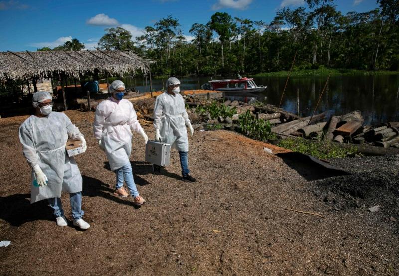 5月23日,医疗人员到达巴西帕拉州马拉若岛的梅尔加苏为当地原住民进行新冠病毒检测。 新华社 图