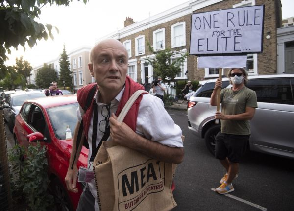 英国首相高级顾问卡明斯当地时间25日回家时,一名抗议者高举标语对他违反居家令表达不满。(欧洲新闻图片社)