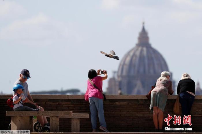 曾经一度成为全球新冠肺炎疫情最严重的国家的意大利终于迎来了一些生活的喧嚣,当地时间5月12日,意大利罗马,人们从露台上眺望景色,拍摄圣彼得大教堂雄伟的穹顶。