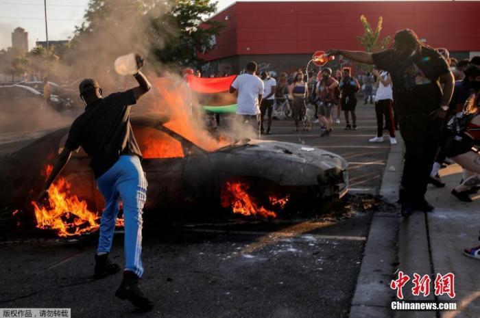 明尼阿波利斯市示威者点燃停车场的汽车。