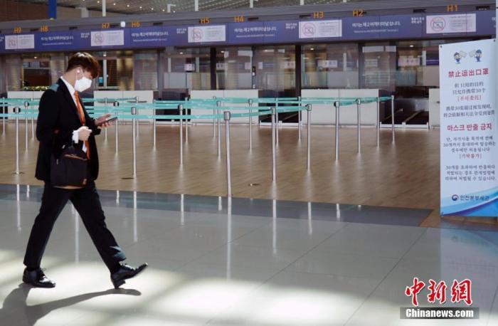 资料图:3月20日,韩国仁川国际机场,工作人员走过机场大厅。中新社记者 曾鼐 摄