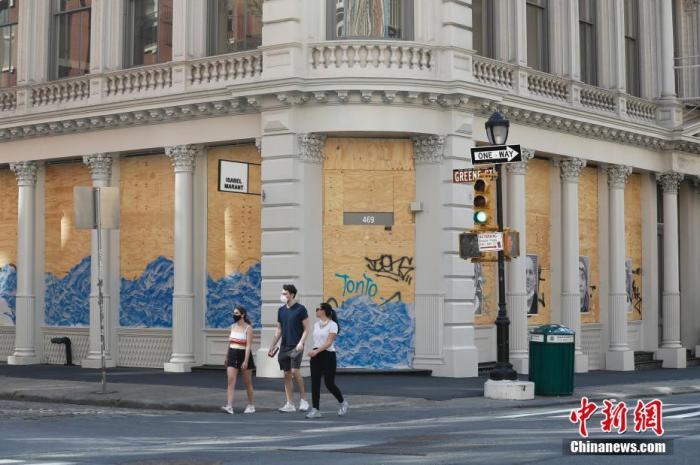 当地时间5月3日,纽约SOHO商业区许多商店仍然用木板封闭着店铺,随着纽约疫情的好转,该商区街头逐渐有稀疏的行人。 中新社记者 廖攀 摄