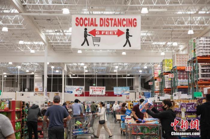 """当地时间5月3日,美国旧金山湾区一家超市挂出提醒顾客保持""""社交距离""""的醒目标识。 中新社记者 刘关关 摄"""