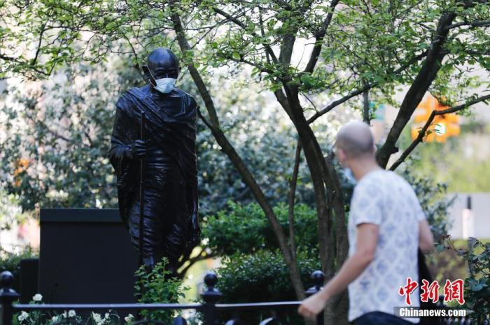 资料图:当地时间5月3日,有人为纽约联合广场的甘地雕塑戴上口罩,引起许多路人注目。 中新社记者 廖攀 摄