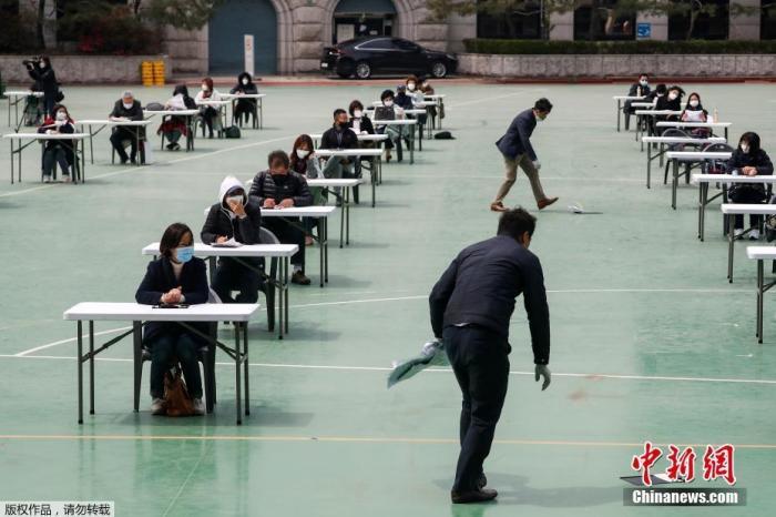 资料图:韩国为了避免新型冠状病毒传播,在露天操场为求职者举行入职考试。图为监考人员在地上捡起被风吹掉的文件。