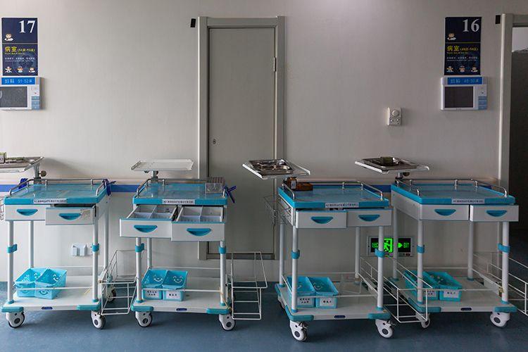 病区走廊里,医务人员使用的小推车集中停放。