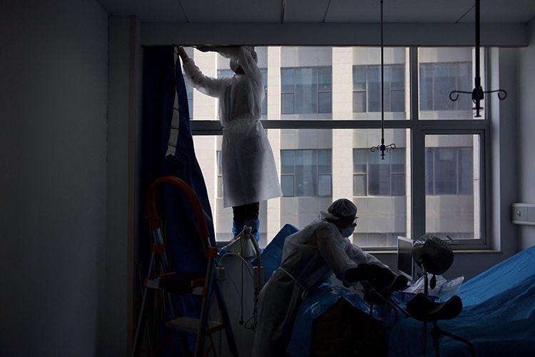 消杀人员正在拆卸病房内的窗帘。