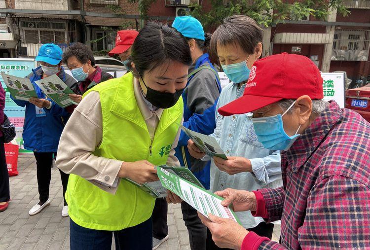 自愿者为住民发放垃圾分类宣传资料。