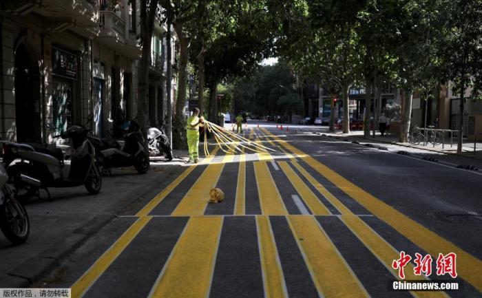 图为巴塞罗那街道上,工人们扩展人行道面积,以便利行人保持社交距离。