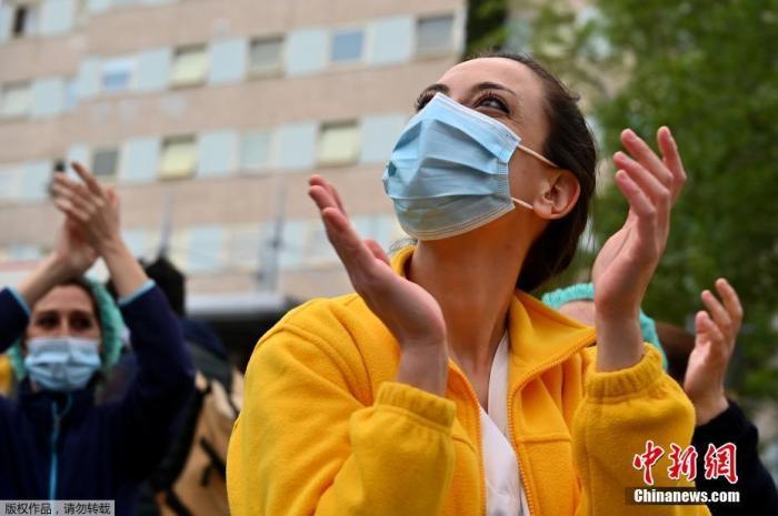 当地时间4月27日,在西班牙马德里的一家医院外,医护人员在为全国禁闭期间居家隔离的民众们鼓掌欢呼,为他们加油打气。