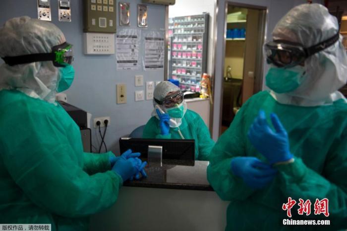 当地时间4月16日,在西班牙西北部维戈的Povisa医院重症监护室,医护人员在护理新型冠状病毒患者之前,穿着全套防护装备聊天。