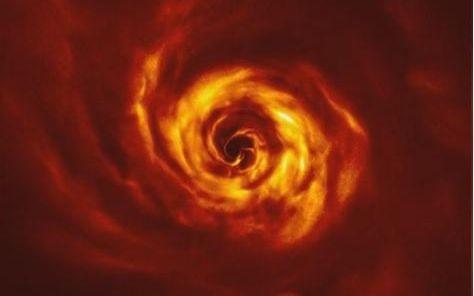"""围绕御夫座AB星旋动的圆盘内出现""""扭曲"""",科学家认为那是行星正在形成的位置。"""