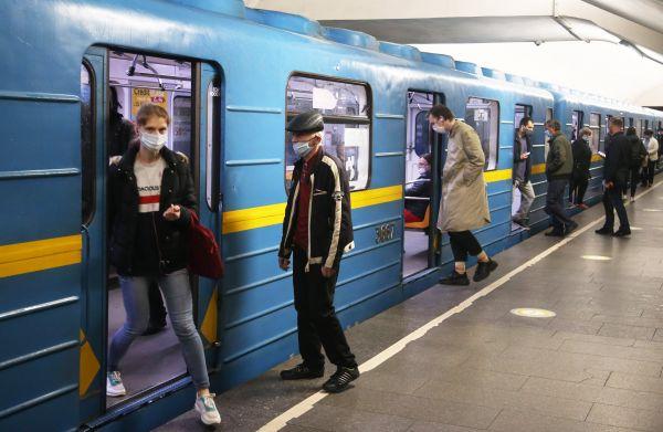 5月25日,乘客在乌克兰基辅市一地铁站内佩戴口罩上下车。新华社发