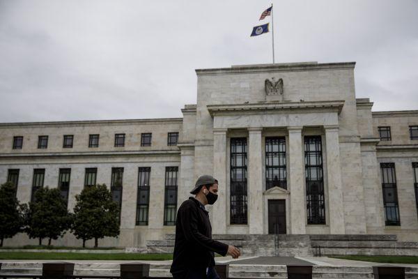 近日,在美国首都华盛顿,一名男子戴着口罩从美联储大楼前经过。新华社发