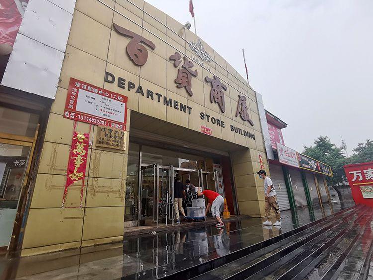 工作人员将一组检测设备装上平板车,推进大楼,进入商场进行环境检测。