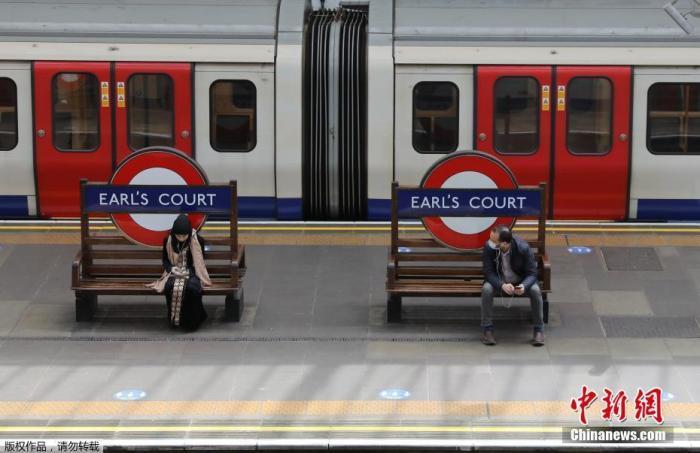 """资料图:英国""""有条件解封"""",出行的伦敦市民坐在伯爵法院站的长凳上。"""