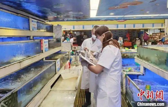 资料图:疾控职员在成都一海鲜市场取样。成都会卫健委供图