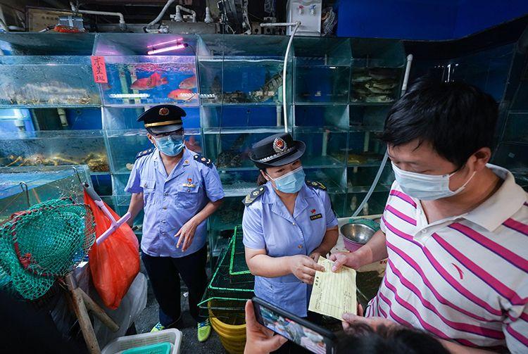 在海鲜水产大厅一家摊位前,市场监管局工作人员检查商户的进货票据。