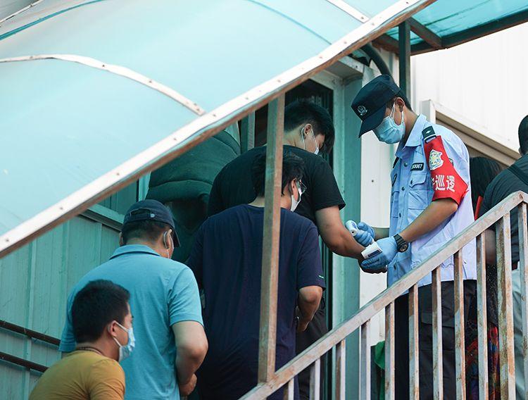 工作人员对商户和职工检测体温。