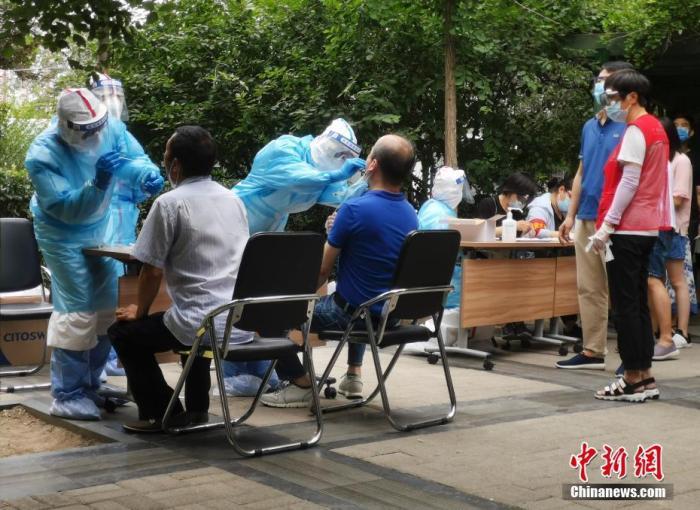 6月17日,北京西城一实行关闭治理的社区,事情职员为社区住民举行核酸检测。中新社记者 杜洋 摄