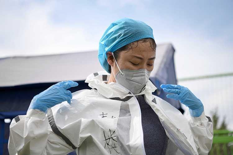 间歇时,医护职员脱下防护服,吹风透气。