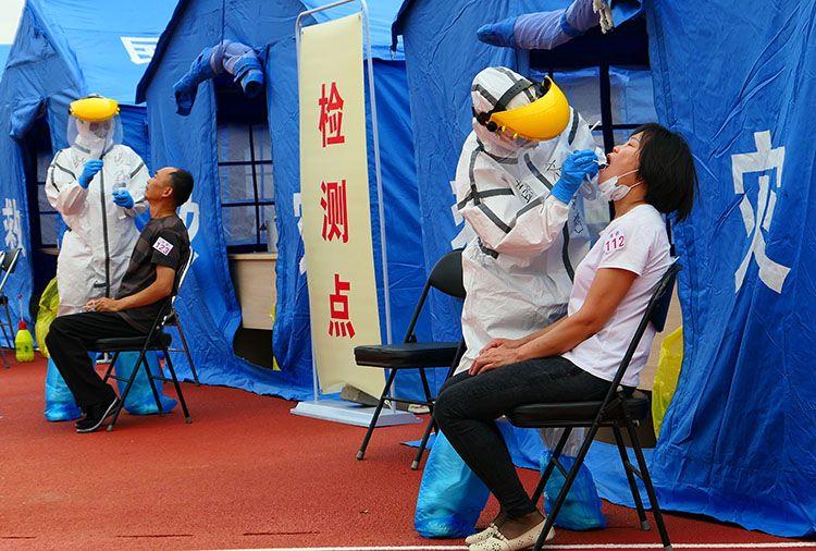 天坛体育中央核酸检测点,医护职员正在对每位挂号的住民举行咽拭子收罗。