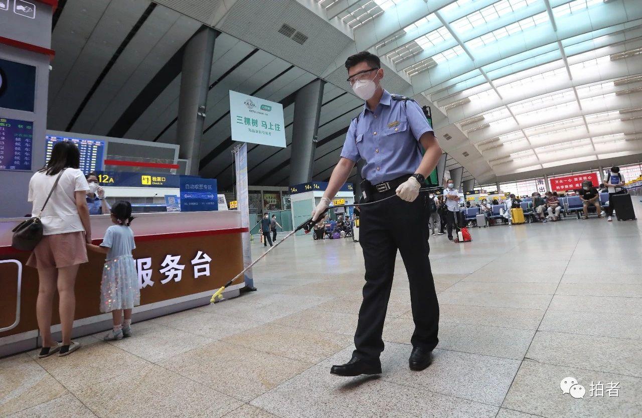 △6月17日,北京南站,车站事情职员戴着口罩、背着喷壶,在大众地区举行消毒。拍照/新京报记者王贵彬
