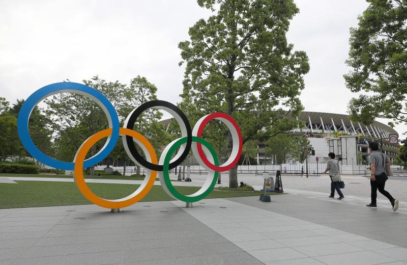 """图说:这是6月12日在日本东京拍摄的五环标志和东京奥运会主场馆""""国立竞技场""""一角。"""