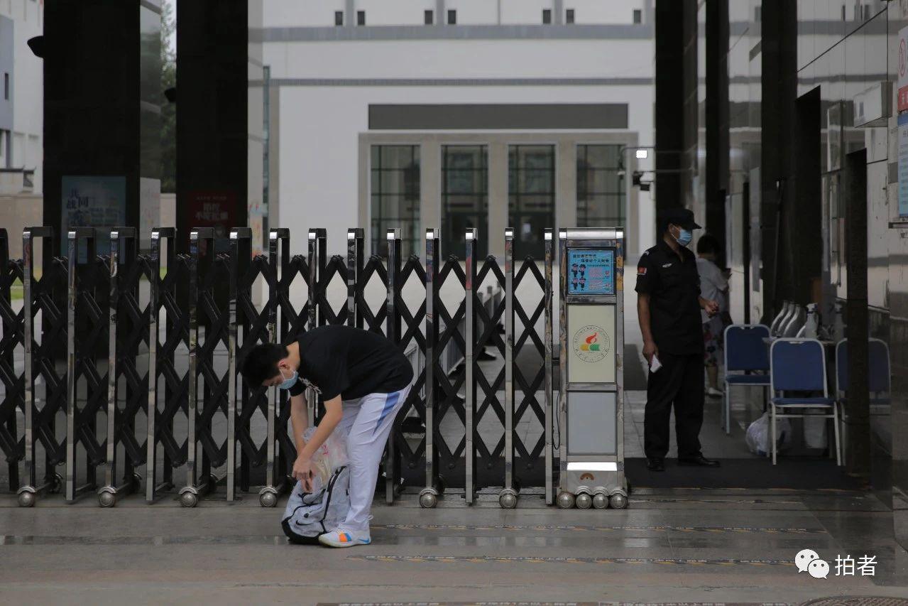 △6月17日,北京市八一学校门口,一名门生摒挡书包脱离校园。拍照/新京报记者郑新洽