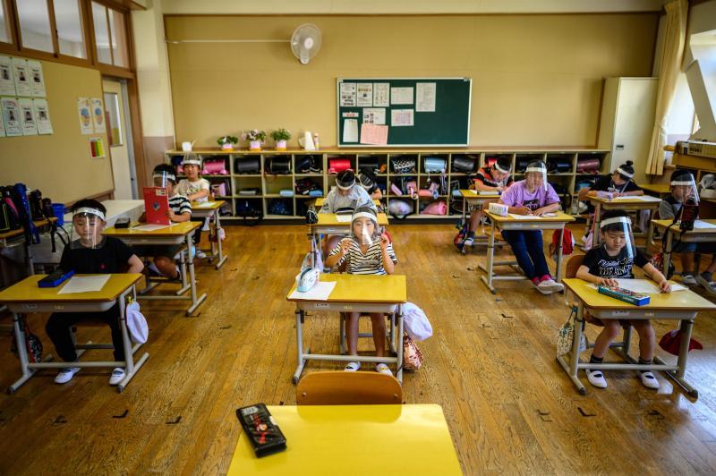图说:6月5日,在日本枥木县日光市一所小学,学生们戴着防护面罩上课。