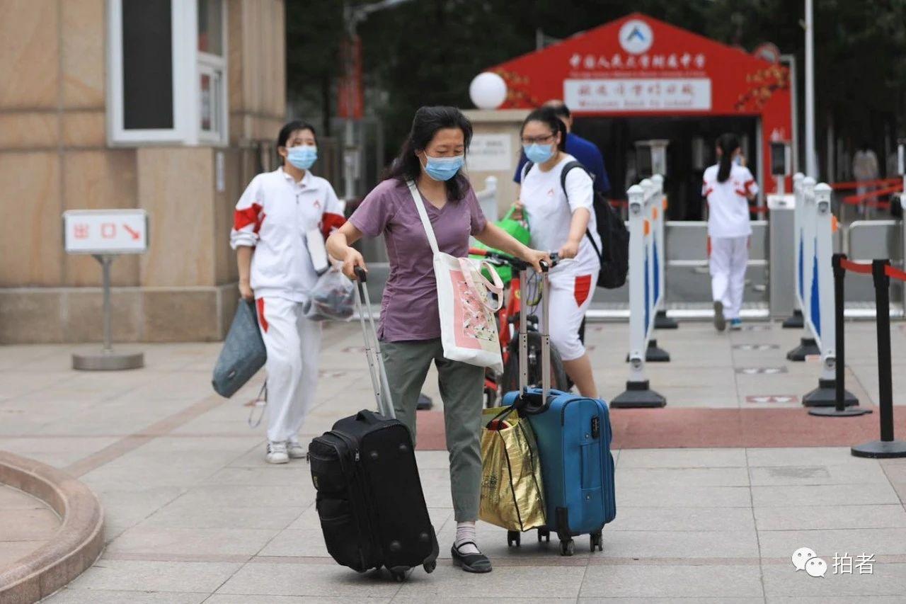 △6月17日上午,人大附中校门口,家长帮孩子搬运行李。拍照/新京报记者浦峰