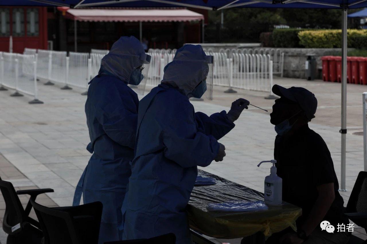 △6月17日,大观园南门广场的会合采样点,住民担当咽拭子收罗。拍照/新京报记者王嘉宁