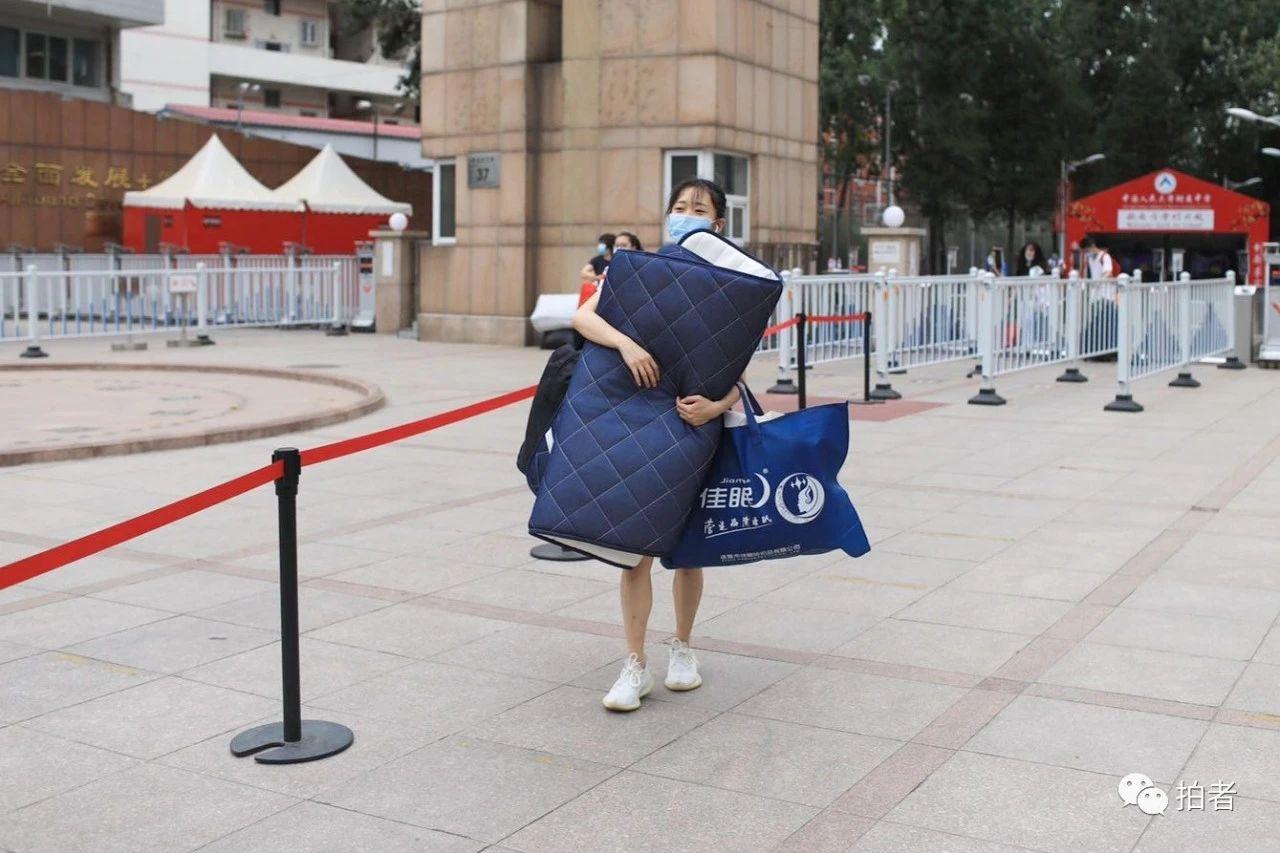 △6月17日上午,人大附中校门口,一位留宿生抱着被褥走出学校。拍照/新京报记者浦峰
