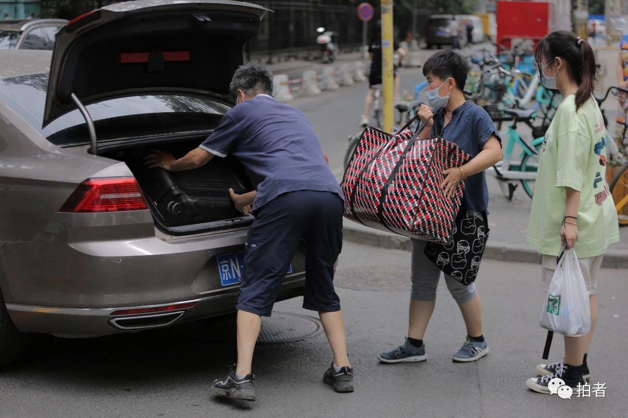 △6月17日上午,北大附中门口,门生家长帮孩子搬行李。拍照/新京报记者郑新洽